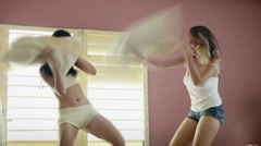 Young adult women fighting with pillows - stock footage