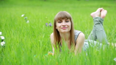 Young woman lying on grass and smiles. Stock Footage