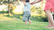 Baby first steps on grass, dolly shot Stock Footage