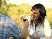 Happy couple drinking wine in the garden, dolly shot Stock Footage