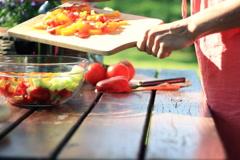 Woman preparing salat in the garden, dolly shot Stock Footage