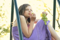 Smiling preteen girl eating green grapes - stock footage