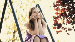Sad preteen girl sitting in the park - stock footage