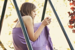 Preteen girl texting on mobile phone in the park Stock Footage