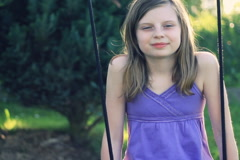 Preteen girl swinging and smiling Stock Footage