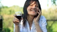 Beautiful happy woman drinking wine and taking on cellphone Stock Footage