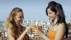 Two girls on holiday in Cuba, toasting with cocktails and drinking Stock Footage