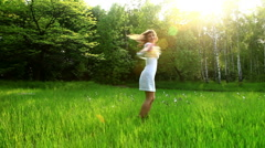 Beautiful woman spinning in the grass. Dolly HD - stock footage