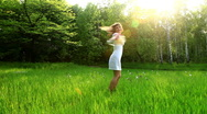 Beautiful woman spinning in the grass. Dolly HD Stock Footage