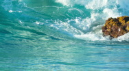 Slow Motion Clear Green Wave Crashes Over Rock on Sandy Beach Stock Footage
