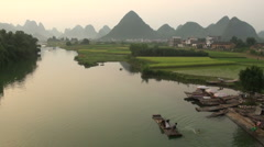 Tourist rafts amidst karst scenery near Yangshuo town, China Stock Footage