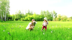 Young mother and child with flowers in the field. Look at Camera. Dolly Stock Footage