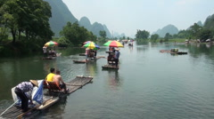 Tourists enjoy ride on bamboo rafts in beautiful natural setting, China Stock Footage