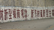 Two motorbikes ride past Communist slogan Stock Footage