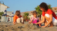 Mom and two kids are making sand pile Stock Footage