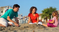 Father, mom and daughter, are playing sand Stock Footage