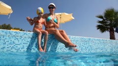 Woman and daughter, sits on pool border and wet feet Stock Footage