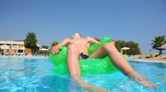Boy sitting on an inflatable chair in the pool water - stock footage