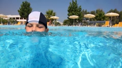 Boy in swimming cap in the pool water Stock Footage