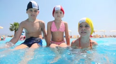 Boy and girls sitting in the pool, the boy splashes water Stock Footage