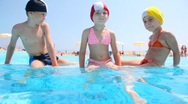 Stock Video Footage of The boy and girls sitting in the pool