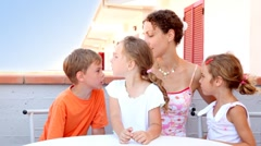 Woman and three kids are sitting at balcony Stock Footage
