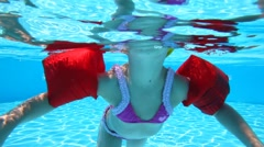 Little girl floundering in the pool water Stock Footage