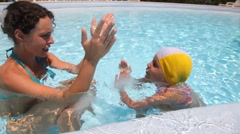 Mother and daughter are in the pool water Stock Footage