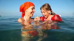 Mom plays with daughter in the water Stock Footage