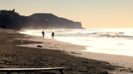 Surfers on shore 03 - walking down beach at sunset Stock Footage