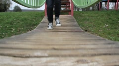 Girl jumping, playing on playground bridge Stock Footage