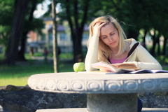 Unhappy female student with to much to learn in the park, dolly shot NTSC - stock footage