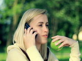 Happy woman holding apple and talking on mobile phone NTSC Stock Footage