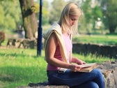 Stock Video Footage of Young female student reading book on stone wall in the park, dolly shot