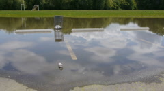 Flooded parking lot. Bottle floating in the foreground. Stock Footage