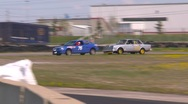 Stock Video Footage of motorsports, Chumpcar race, #3 follow shot in corner Dodge Neon and Volvo