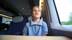 Smiling boy sits and looks out of window train during movement Stock Footage