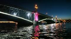 Camera moves at night under lighted iron bridge standing on Neva Stock Footage