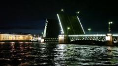 Dry cargo ship floats through raised bridge night on Neva river Stock Footage