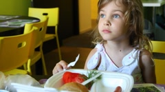Girl smiling and watches TV while eating at table Stock Footage