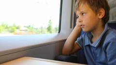 Boy sits and looks out of window trains during movement has leaned cheek against Stock Footage