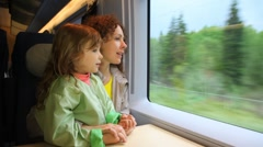 Mother with daughter ride in speeding train and look at window - stock footage