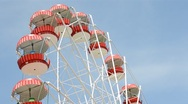 Stock Video Footage of Brightly colored Ferris wheel against the blue sky