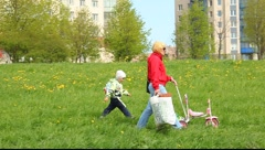 Mother with a baby walking on the grass Stock Footage