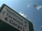Stock Video Footage of London Heathrow sign with Plane Overhead, London England GFSD