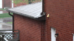 Heavy rain pouring off rain gutter on side of a brick house Stock Footage