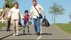 Family: mother, father and daughter learning inline skates Stock Footage