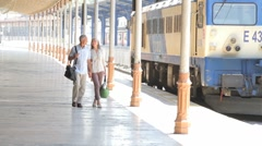 Couple walking on rail station platform, holding hands Stock Footage