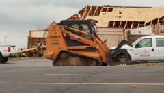 Skid Steer Driving Down a Road After Tornado (HD)m Stock Footage