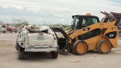 Skid Steer cleaning up wrecked car (HD) c - stock footage